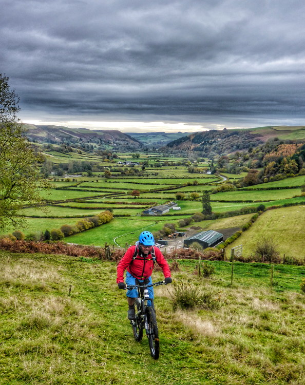 Cycling the Trans Cambrian Way with patchwork green fields in the background