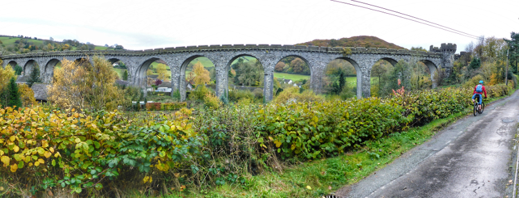A panoramic shot of a cyclist riding along the road with an impressive viaduct in the background