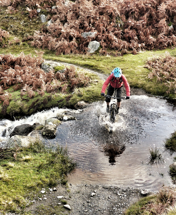 Mountain biker splashes through an overflowing river on the Trans Cambrian Way