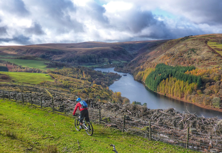A cyclist rides along the Trans Cambrian Way with the Claerwen Reservoir below