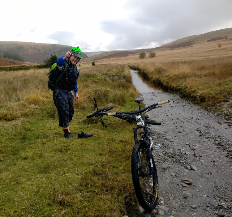 A cyclist stops to squeeze out a sock after a particularly wet section of the Trans Cambrian Way