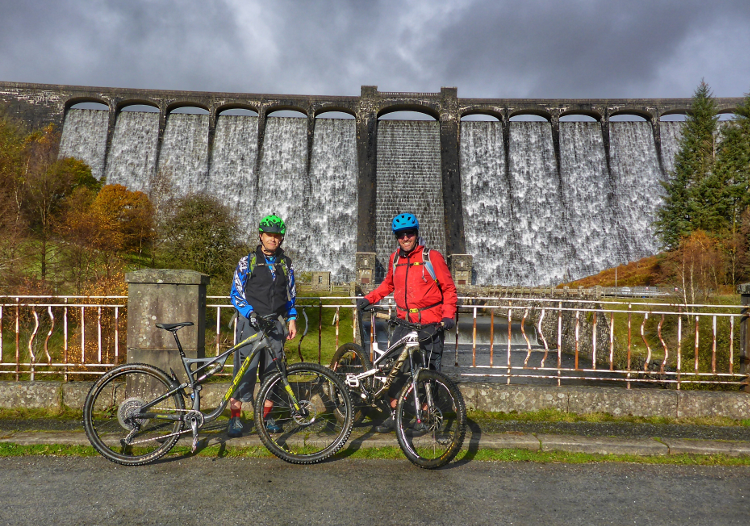 Two cyclists pose with their mountain bikes beneath a dam on the Trans Cambrian Way