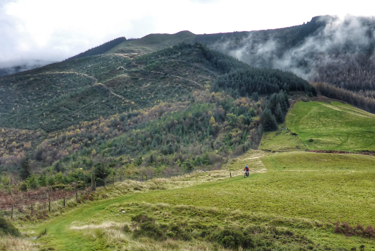 A cyclist in the distance, dwarfed by the wooded and grassy hillside of the Trans Cambrian Way