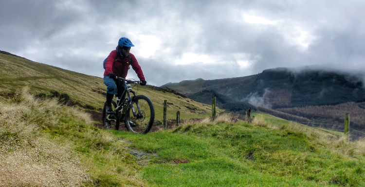 A mountain biker summits a slight slope on the Trans Cambrian Way