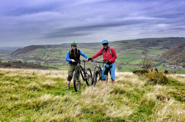 Two mountain bikers out on the Trans Cambrian Way, surrounded by open hills
