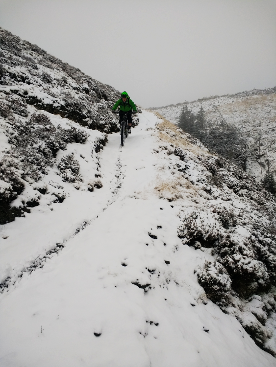A mountain biker riding the Trans Cambrian Way in a blizzard