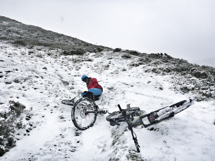 A cyclist takes a spill in the snow