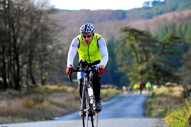 A man cycling in winter cycling clothes, including brightly coloured bib